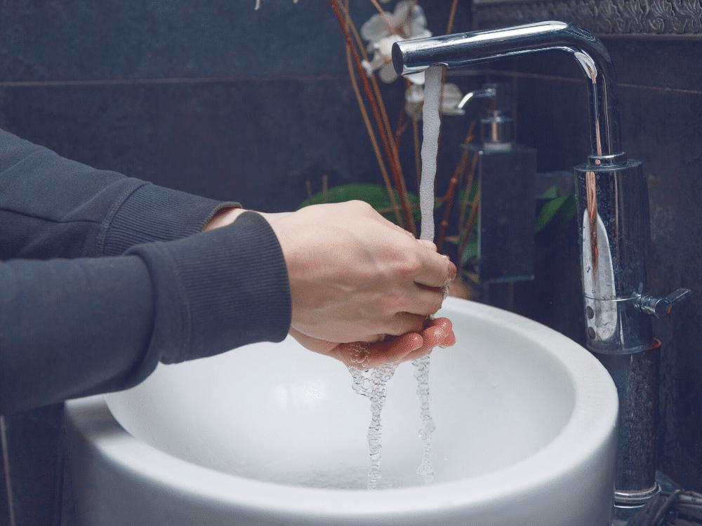 Kvinde, som vasker sine hænder under en vandhane